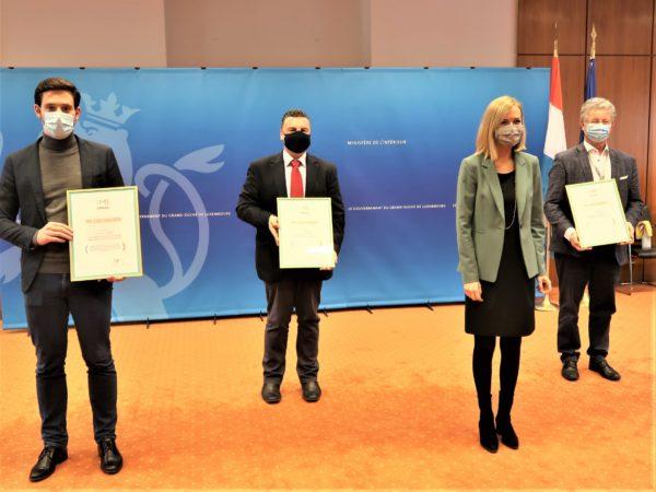 Taina Bofferding avec les représentants des trois communes-pilotes montrant leur Prix d'encouragement.